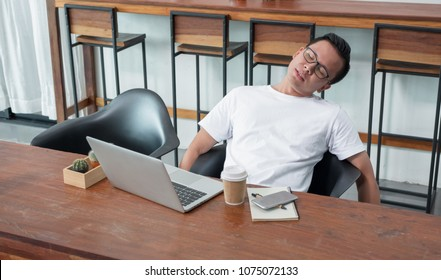 asia casual man sit back feel tired from work at laptop in coffee shop,stress business concept,work outside office,work at home