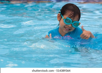 Asia Child having fun in swimming pool. Kid playing outdoors