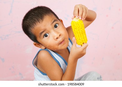 Asia children eats corn with happy mood.