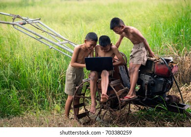 Asia children student use laptop for learning and knowledge about technology media and internet network out of classroom with field rice background, Education concept.