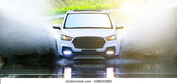 Asia, China, Shanghai - October 26, 2017: Car tester drives white suv of new car into wading area to test wading depth, resulting in splashing sewage