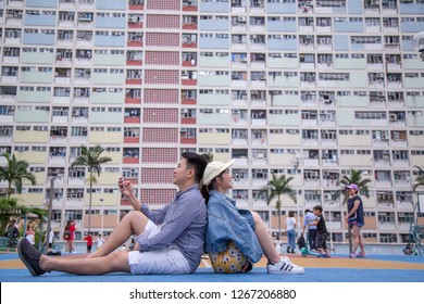 Asia couple setting by rear to rear with rainbow design building of Choi Hung Estate. Located in Wong Tai Sin district of Kowloon, Hong Kong.