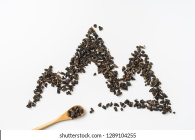 Asia culture and design concept - fresh taiwan oolong tea and cup with mountain shape made by dry tea dust