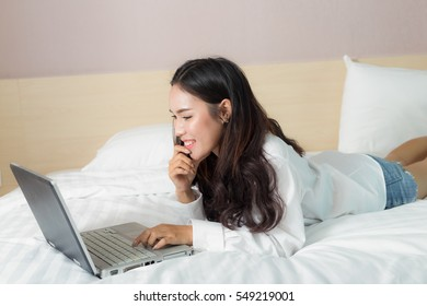 Asia cute girl with computer notebook on the bed.