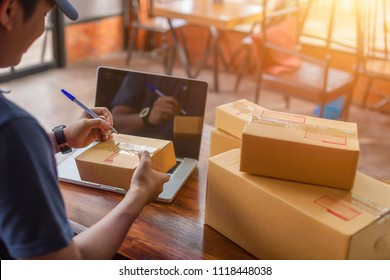 Asia delivery man are holding a cardboard box delivery to his customer.Delivery man are checking to his customer,The seller prepares the delivery box for the customer, online sales, or ecommerce.