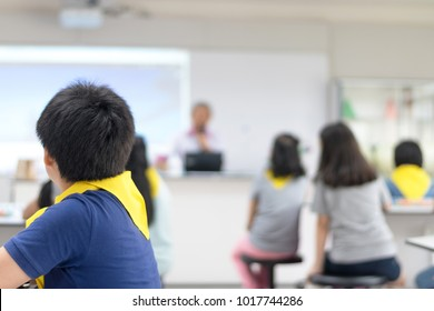 Asia elementary students in science class. Group of schoolboys and schoolgirls attend in classroom with scientist teacher teaching in front of room. STEM education concept.