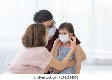 Asia Family in medical masks on the face looks at the camera while standing in the living room at home to prevent PM2.5 dust, smog, air pollution and COVID-19. Healthcare concept.