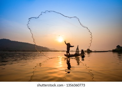 Asia fisherman net using on wooden boat casting net sunset or sunrise in the Mekong river / Silhouette fisherman boat with mountain background people life on countryside