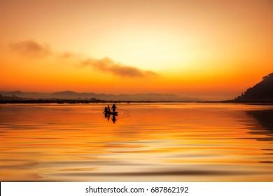 Asia Fisherman on boat fishing at river.