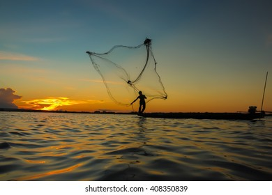Asia fishermen fishing in the river at sunset.