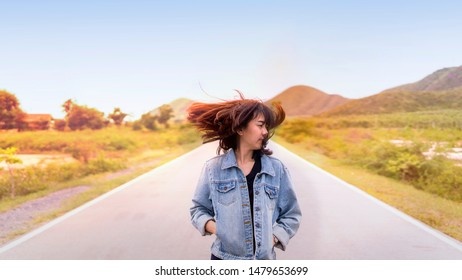 Asia girl flicking hair on a Deserted road in sunset time