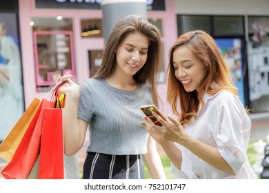 Asia girl and friend ethnic German-Thai go shopping holding bag and smart phone in a department store.