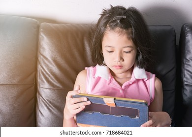 asia girl happy play tablet on the black color sofa