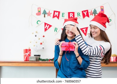 Asia girl lovers couple,girlfriend close eye to surprise friend by giving Christmas present  at house party,Holiday celebrating season,Lovely lesbian couple.
