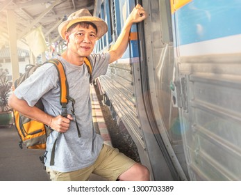 Asia happy smailing backpacker man wear hat stepping up to a train.Handsome  passenger at train station.Travel concept.