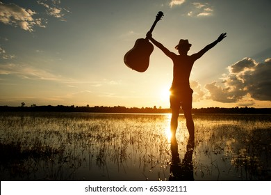 Asia hipster man.Musician holding acoustic guitar and standing in water at sunset