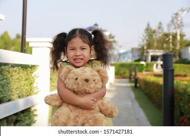 Asia kid girl stand smile hugged a teddy bear in the park.