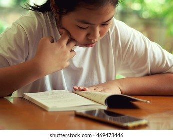 Asia lady reading her book to prepare examination in vintage style and don't interested in social network on her smart phone