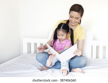 Asia little girl & mother reading book on the bed, mother and daughter reading book together