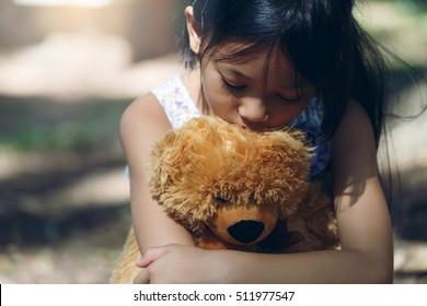 Asia Lovely girl sad mood Hug teddy bear at under the big tree
