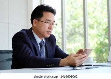 Asia man CEO, Asian businessman using phone while working at office, CEO business asian man with smart phone for communication while sitting in office, people business and technology concept