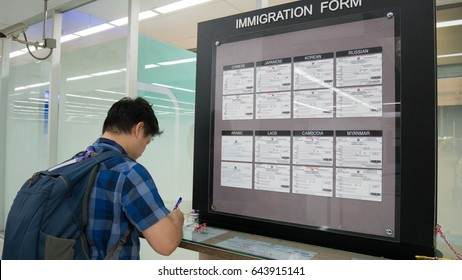 Asia man traveler filling immigration form on immigration form at customs service area in airport. Immigration form concept.