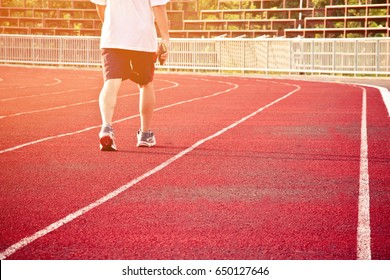 Asia man walking in racetrack in outdoor stadium with sunlight. Hand holding mobile smart phone. A man Age between 50-60 years. Walking is a healthy exercise.