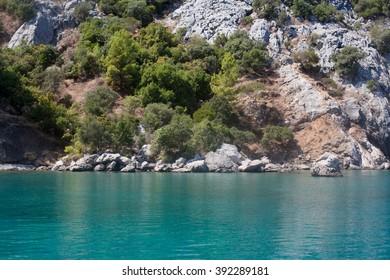 Asia Minor; Turkey; Mediterranean; sea; Chirali; nature; horizontal; outdoor; blue; day; grey; sunny; sunlight; rock; stone; white; water; wave; peddle; green; tree; flora; coastline