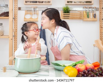 asia mother and daughter happy cooking food in kitchen funny together