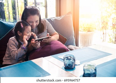 Asia mother and daughter or kid enjoy playing smartphone, happy family using mobile phone