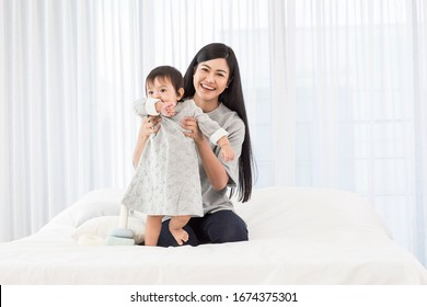 Asia mother hugs and play  baby  at white  room in the morning