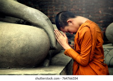 Asia novice monk worship the Buddha with faith.Buddhist monk sacred Buddha statue depicting a religious faith in a temple in country Southeast Asia.