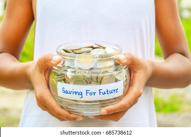 Asia rural boy with white vest holding a glass bowl full of Thailand coins, concept saving for the  future.For children education,emergency.Include National Teach Children to Save Day.
