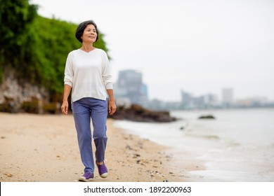 Asia senior happy woman is walk and exercise on the Calm beach in the morning alone.