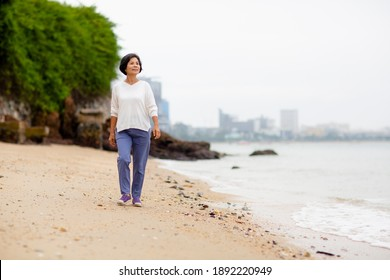 Asia senior happy woman walk and exercise on the Calm beach in the morning. Coronavirus the end concept.