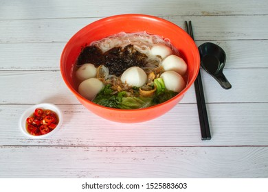 Asia Singapore noodle with fish ball vermicelli soup minced pork with cut red chilli padi, green vegetables, and fresh fried ikan billis fishes.