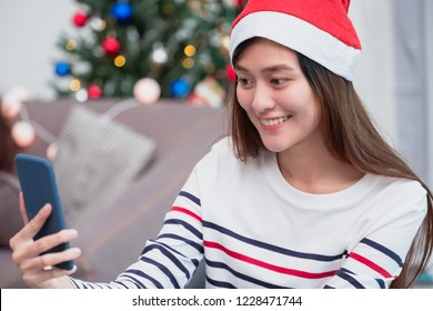 asia smile woman take selfie photo with mobile phone with blur christmas tree at xmas party,Live streaming video on social media event,Christmas holiday celebration party