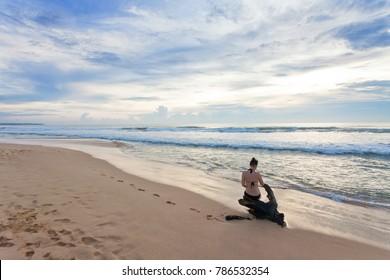 Asia - Sri Lanka - Ahungalla - A woman sitting on a stump at the beach