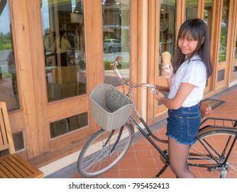 Asia teenage girl eat green tea ice cream cone at restaurant