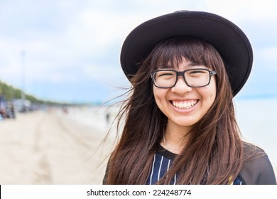asia teenage girl with eyeglasses and hat with blur beach background