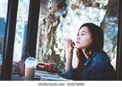 Asia teenage sitting in thinking alone with make a note in coffee bar.