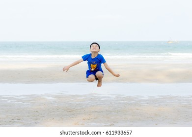 Asia Thai boy are enjoying to jump at beach.