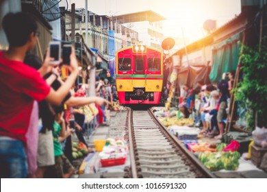 Asia tourists taking photo a train coming and pass the fresh market by amazing on vacation.Talad Rom-Hoob Samutsongkram Thailand.