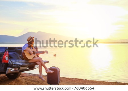 Asia traveler sitting hatchback car and playing guitar when sunset near the lake on holiday.beautiful tourist watch view of nature on vacation.