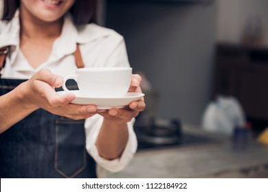 asia woman barista wear jean apron holding hot coffee cup served to customer with smiling face at bar counter,Cafe restaurant service concept.waitress working
