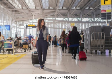 Asia woman carries luggage on blur airport terminal background.