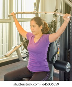 Asia woman concentrate enjoy sport machine in fitness club with yellow light of sun