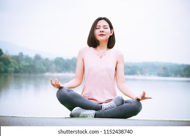 Asia woman doing yoga fitness exercise for relax and healthy in morning park. Concept outdoor sport and health. use vintage filter. Calmness and relax, female happiness. Freedom concept.