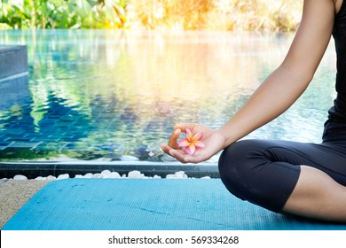Asia woman doing yoga fitness exercise for relax and healthy beside palm tree and blue sky reflect in swimming pool , Concept outdoor sport and health use filter effect