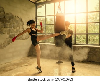 Asia woman in a fitness suit is kicking a sandbag in the gym and the coach is the sandbag catcher.